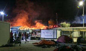Migrants and riot police stand outside the Moria refugee camp as a fire burns part of the facility.