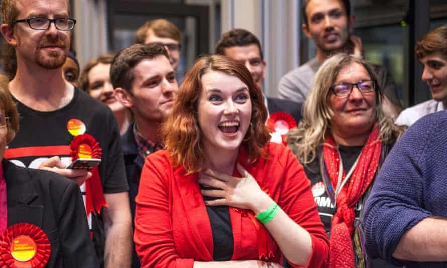 Labour supporters celebrate while watching a tv as result comes in