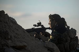 A fighter with the Syrian democratic forces keeps position at a hilltop as he watches the Islamic State's last remaining location in the village of Baghuz.