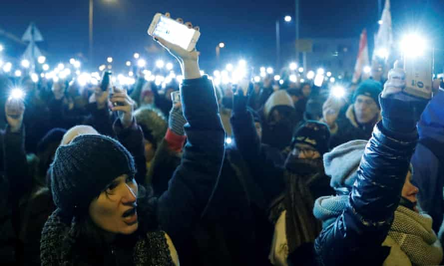 People hold up their mobile phones attend a protest against the proposed new labor law.