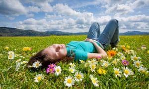 a young woman lying in a meadow with flowers
