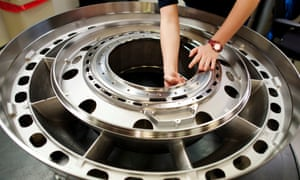 A worker checks the quality on an aircraft engine component