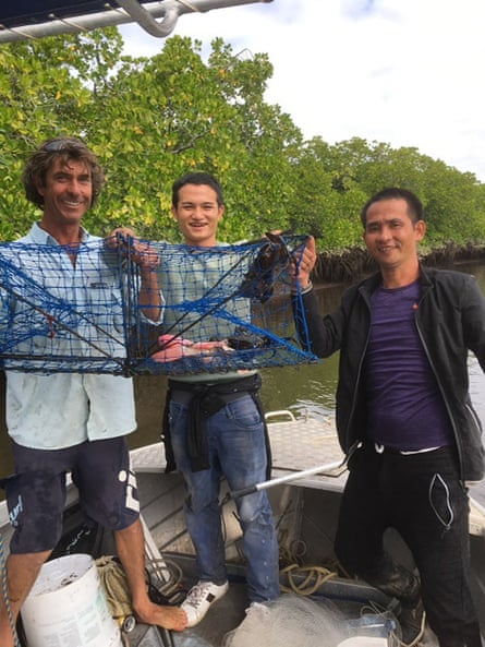 A Queensland fisherman (left) treats two suspected asylum seekers to a tour after being found on the banks of the Daintree River.