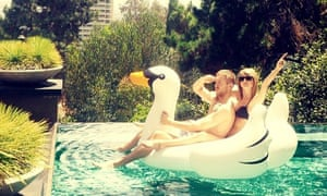 Taylor Swift and Calvin Harris ride on an inflatable swan.