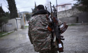An ethnic Armenian soldier carries weapons in Martakert province, Nagorno-Karabakh.