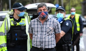 A man is detained during an anti-lockdown protest in Melbourne. At least 14 people were arrested and 51 fines issued