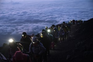 A group of hikers climb to the top of Mount Fuji just before sunrise.
