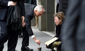 Former prime minister Malcolm Turnbull gives a homeless man five dollars