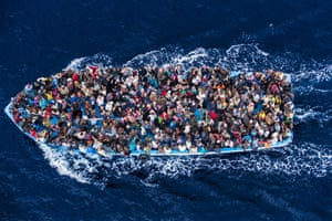 Migrants risk everything for a new life in Europe. African asylum seekers photographed from an Italian navy helicopter shortly before being rescued on the Mediterranean Sea. 8 June 2014.