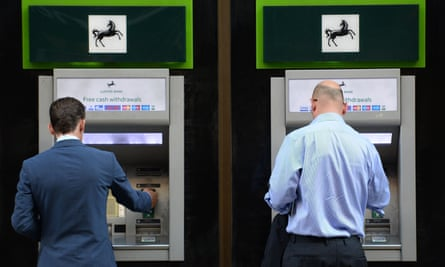 Two men use ATMs