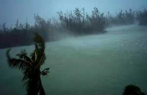 Strong winds from Hurricane Dorian blow the tops of trees and brush while whisking up water from the surface of a canal that leads to the sea, located behind the brush at top, seen from the balcony of a hotel in Freeport, Grand Bahama, Bahamas, Monday, Sept. 2, 2019. Hurricane Dorian hovered over the Bahamas on Monday, pummeling the islands with a fearsome Category 4 assault that forced even rescue crews to take shelter until the onslaught passes.