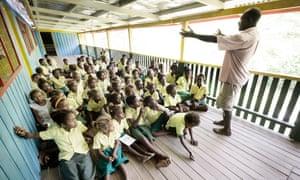 A primary school teacher talks to a class of children