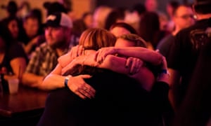 Women hug at a fundraiser for victims and their families at Stoney's Rockin' Country bar in Las Vegas.