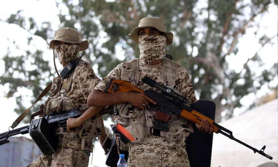 Libyan forces loyal to the Government of National Accord keep watch from a position south of Tripoli.