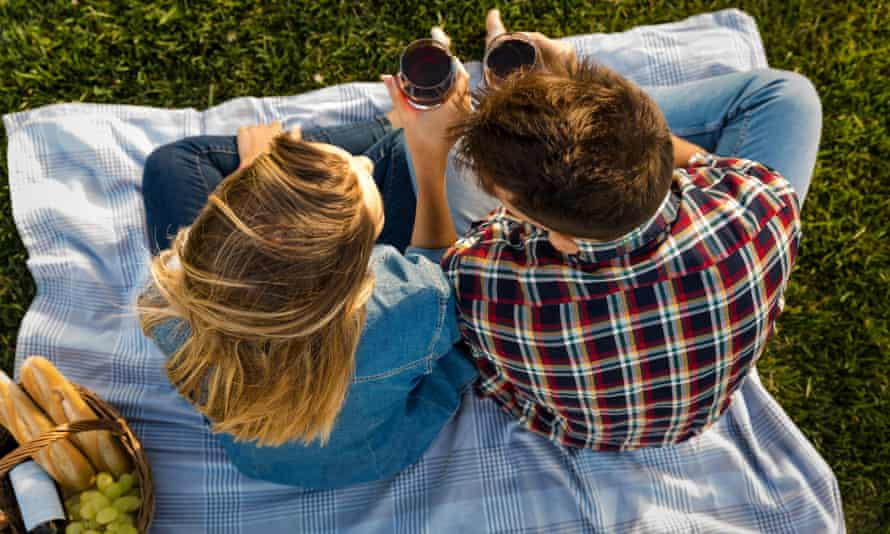 A couple enjoy a day in the park making a picnic.