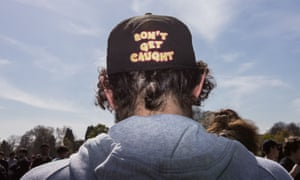 A man wears a 'Don't get caught' hat during the rally
