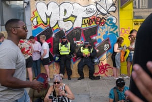 Met police lean against a wall.