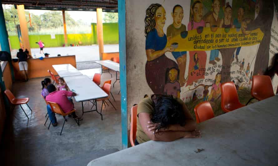 A woman rests her head on a table inside La 72, a shelter for migrants in Mexico.