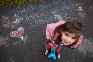18 March 2020 - Vicky Sergeant and her daughter Kleio writing chalk messages of support for NHS workers at the Royal Preston hospital in Lancashire