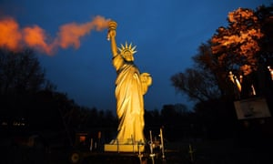 A picture taken on November 16, 2017 shows a replica of the Statue of Liberty emitting smoke from the torch created by Danish artist Jens Galschiot and displayed at the Rheinaue park during the COP23 United Nations Climate Change Conference in Bonn, Germany.