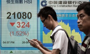 Pedestrians in Hong Kong walk past an electronic board displaying the benchmark Hang Seng index.
