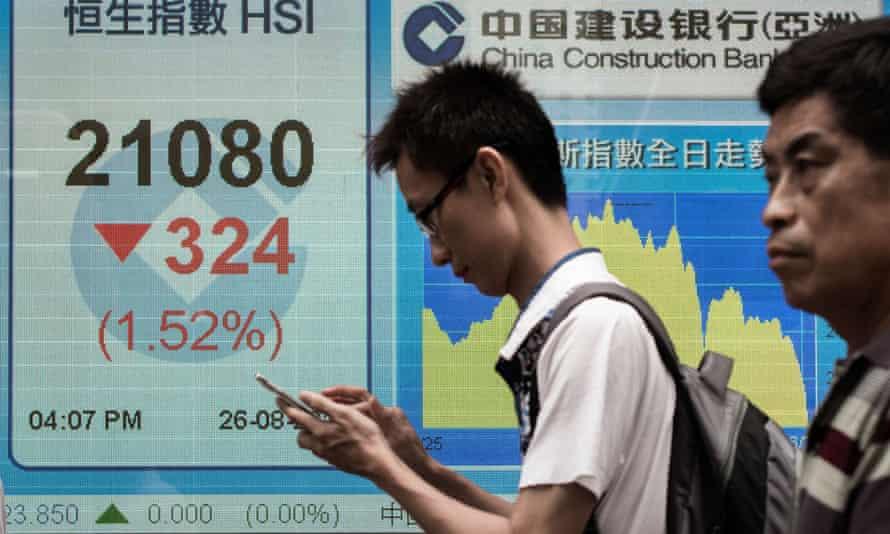 Pedestrians in Hong Kong walk past an electronic board displaying the benchmark Hang Seng index.