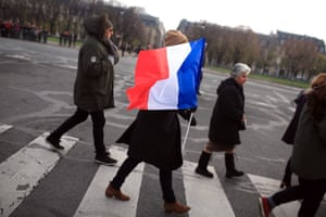 A woman holds a French flag as she crosses the road outside the Invalides