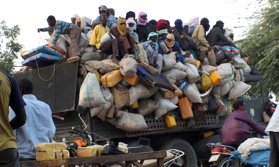 Migrants sit on top of a truck about to leave the city of Agadez in Niger