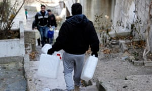 A man carries empty jerry-cans to be filled with water in Damascus, Syria