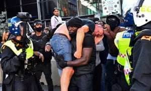 Patrick Hutchinson carries an injured counter-protester to safety, near Waterloo station during a Black Lives Matter protest.