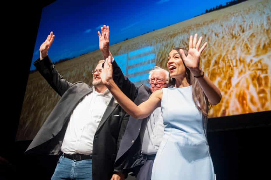 Congressional candidate James Thompson, Senator Bernie Sanders and Alexandria Ocasio-Cortez, wave at the end of the campaign event.