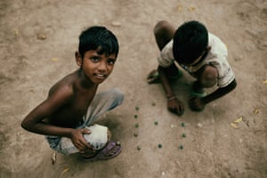Two boys playing a game of marbles in a back street of Kolkata.