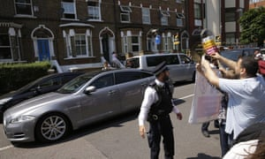 People hold a small demonstration as the car carrying British Prime Minister Theresa May leaves the scene where a van struck pedestrians, in Finsbury Park, north London.