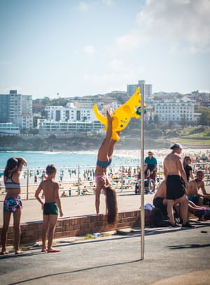 A girl does a handstand on the wall in front of Bondi beach