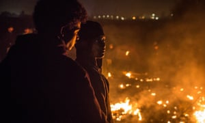 Calais, FranceMigrants watch their makeshift homes burn in the Jungle in Calais, France