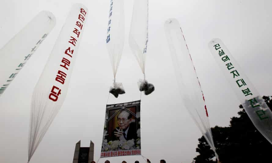 A portrait of deceased North Korean defector Hwang is hung on balloons as former North Korean defectors prepare to release them towards the North