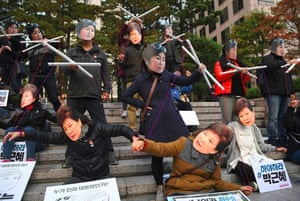 Masked protesters posing as South Korean president Park Geun-hye, depicting her as a puppet being operated by her confidante Choi Soon-sil.