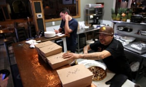 A worker prepares to-go orders at Creekside Pizza and Taproom in San Anselmo, California.