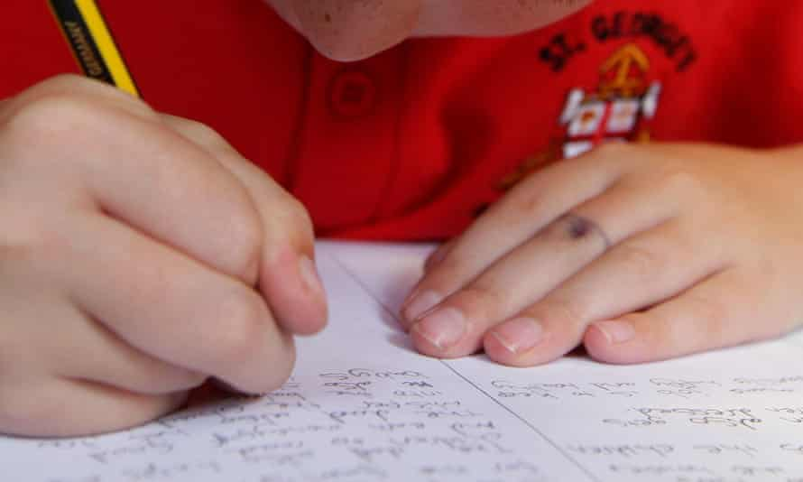 A pupil writing in an exercise book
