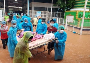 Volunteers in protective suits try to relocate patients who are dependent on oxygen from the Covid-19 centre due to the floods in Myawaddy, Karen state, Myanmar.