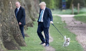 Boris Johnson walks his dog Dilyn, with a minder