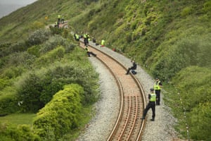 Officers stand guard along the railway line at Carbis Bay