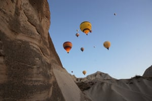 Hot air balloons glide over the historical and Unesco world heritage site in Cappadocia
