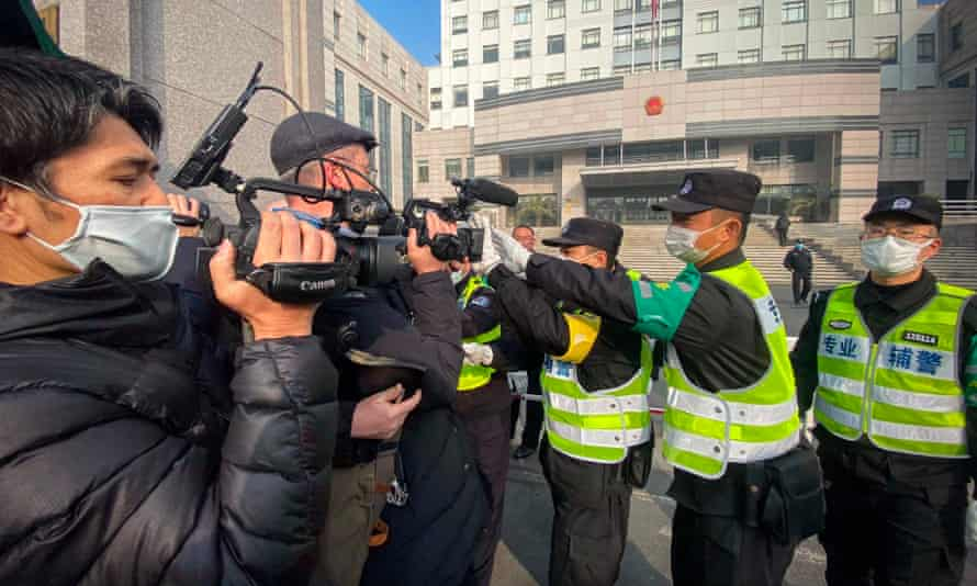 Police attempt to stop journalists from recording footage outside the Shanghai Pudong New District People's Court, where Chinese citizen journalist Zhang Zhan was on trial