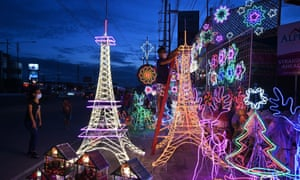 A worker wearing a face mask fixes a decoration shaped like the Eiffel tower next to others displayed for sale on a road in San Fernando, Pampanga province in the Philippines, 6 October 2020.