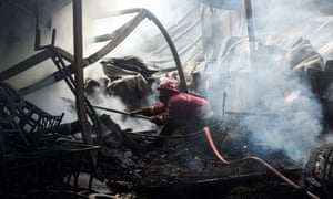 A firefighter tries to extinguish a warehouse fire in the Depok district of West Java, Indonesia