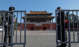 Security guards wearing a protective face masks stand near an entrance of the Forbidden City in Beijing, China, 20 April 2020.