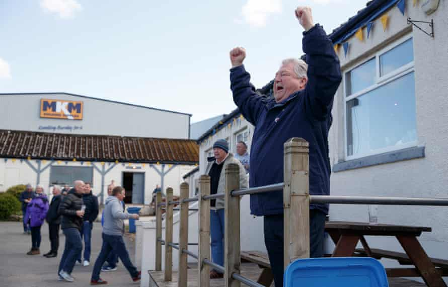 A member of the 'Lowerhouse Ultras' cheers on the home team from his usual position in front of the clubhouse.