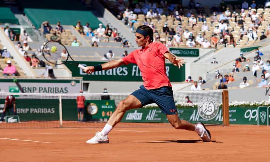 Roger Federer makes a backhand return.