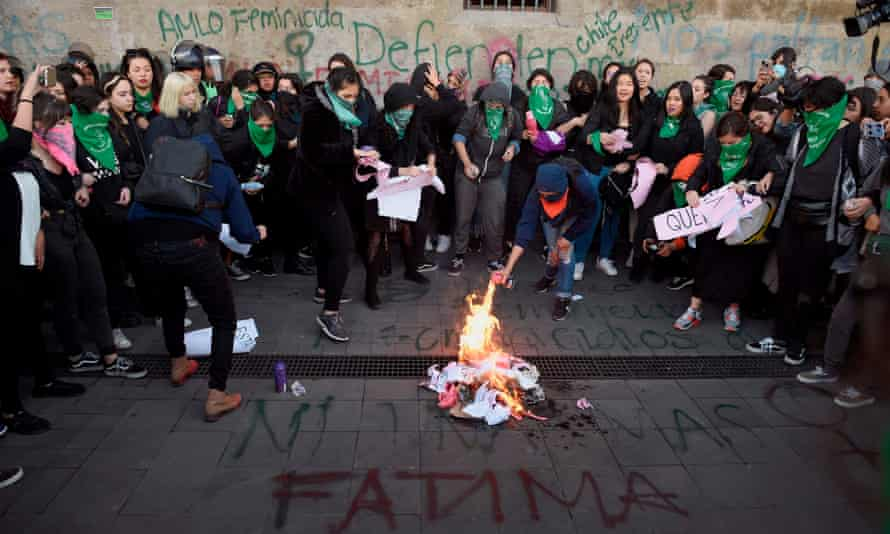 Demonstrators start a fire as they gather outside the national palace in Mexico City, Mexico, on 18 February to protest gender violence.